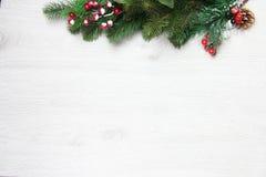 Weihnachten- und neues Jahr ` s Zusammensetzung Die Kiefernkegel, Fichtenzweige auf einem hölzernen weißen Hintergrund Lizenzfreie Stockfotos