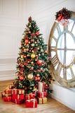 Weihnachten und neues Jahr verzierten weißen Innenraum mit Geschenken und Baum des neuen Jahres mit rotem Dekorball Graues Sofa u lizenzfreies stockfoto