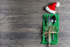 Weihnachten, verziertes Tischbesteck mit einem Sankt-Hut auf einer grünen Serviette, verziert mit einem Zweig der Kiefer und des  Lizenzfreies Stockfoto