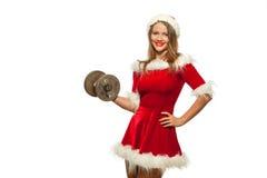 Weihnachten, Weihnachten, Winter, Glückkonzept - Bodybuilding Starke Sitzfrau, die mit Dummköpfen in Sankt-Helfer trainiert Lizenzfreies Stockfoto