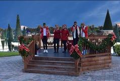 Weihnachtencarolers, die am hellblauen bewölkten Hintergrund im internationalen Antriebsbereich durchführen lizenzfreie stockfotografie