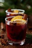Weihnachtenglühwein oder gluhwein mit Gewürzen und orange Scheiben auf rustikaler Tabelle, traditionelles Getränk auf Winterurlau Stockbild
