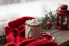 Weihnachtenweißes chaskka mit einem Weihnachtsheißen Getränk am Fenster Lizenzfreie Stockfotografie