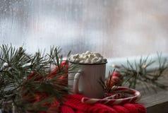 Weihnachtenweißes chaskka mit einem Weihnachtsheißen Getränk am Fenster Lizenzfreies Stockfoto