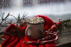 Weihnachtenweißes chaskka mit einem Weihnachtsheißen Getränk am Fenster Stockfotos