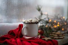 Weihnachtenweißes chaskka mit einem Weihnachtsheißen Getränk am Fenster Lizenzfreie Stockfotos