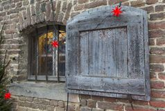 Windows with wooden shutter. The photo shows a Christmas decorated windows with an old wooden shutter royalty free stock photography