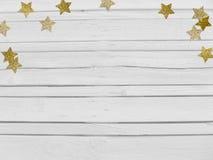 Weihnachts-, des neuen Jahresparteimodellszene mit funkelnden Konfettis der goldenen Sternform und leerer Raum Weißes hölzernes Lizenzfreie Stockbilder