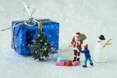 Weihnachts-Feier mit Miniatur-Weihnachtsmann, der Geschenk gibt Stockfotografie