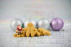 Weihnachts-Lebensmittelphotographie-Lebkuchenmann Mini-Weihnachtsmann und des silbernen Baums Flitter auf Weihnachtspackpapierhin Stockbild
