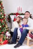 Weihnachts- oder des neuen Jahresfeier Glückliche junge Familie, die im Stuhl nahe Weihnachtsbaum mit Weihnachtsgeschenken sitzt  Lizenzfreies Stockfoto