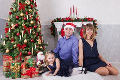 Weihnachts- oder des neuen Jahresfeier Glückliche junge Familie am Weihnachtsbaum mit einem Kamin lizenzfreie stockfotografie
