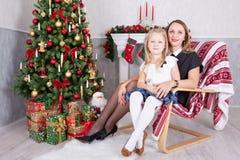 Weihnachts- oder des neuen Jahresfeier Glückliche Mutter und Tochter, die im Stuhl nahe Weihnachtsbaum mit Weihnachtsgeschenken s lizenzfreies stockbild