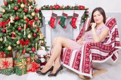 Weihnachts- oder des neuen Jahresfeier Junge Frau in einem festlichen Kleid sitzt in einem Stuhl in einem Weihnachtsinnenraum, na Stockfoto