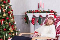 Weihnachts- oder des neuen Jahresfeier Junge Frau in einem Weiß strickte Pullover und Sankt-Hut, hält eine Schale in der Hand und Lizenzfreie Stockfotos