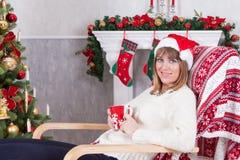Weihnachts- oder des neuen Jahresfeier Junge Frau in einem Weiß strickte Pullover und Sankt-Hut, hält eine Schale in der Hand und Stockbild