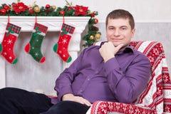 Weihnachts- oder des neuen Jahresfeier Junger Mann sitzt in einem Lehnsessel und hält eine Schale nahe Weihnachtsbaum mit Weihnac Stockfotografie