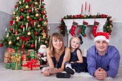 Weihnachts- oder des neuen Jahresfeier Porträt von den netten glücklichen Leuten der dreiköpfigen Familie, die auf dem Boden nahe Stockfotos