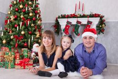 Weihnachts- oder des neuen Jahresfeier Porträt von den netten glücklichen Leuten der dreiköpfigen Familie, die auf dem Boden nahe Stockfoto
