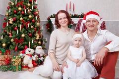 Weihnachts- oder des neuen Jahresfeier Porträt von netten jungen Leuten der dreiköpfigen Familie nahe dem Weihnachtsbaum mit Weih Stockfotografie