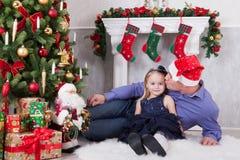 Weihnachts- oder des neuen Jahresfeier Vater küsst die Tochter nahe dem Weihnachtsbaum Vater haben einen Santa Claus-Hut auf sein Lizenzfreie Stockfotos