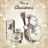 Weihnachts- oder des neuen Jahreshand gezeichnete Vektorillustration Schneemann im Winterhut mit Besen- und Geschenkskizze, Weinl Lizenzfreie Stockbilder