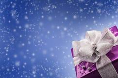 Weihnachts- oder des Valentinsgrußespurpurrotes Geschenk mit silbernem Bandzusammenfassungs-Blauhintergrund Lizenzfreies Stockbild