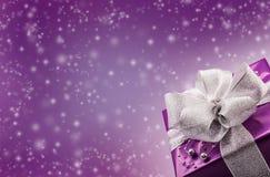 Weihnachts- oder des Valentinsgrußespurpurrotes Geschenk mit silbernem Bandzusammenfassungs-Purpurhintergrund