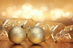 Weihnachts- oder Feiertagshintergrund mit zwei goldenen Verzierungen stockbild