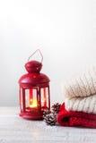 Weihnachts- oder Winterhauptkonzept mit Laterne, Tannenzapfen, Schnee und wärmen Abnutzung stockfotografie
