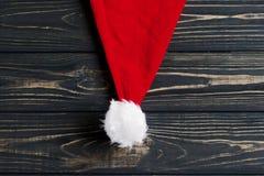 Weihnachts-Sankt-Hut auf stilvollem schwarzem rustikalem hölzernem Hintergrund Stockfotografie