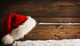 Weihnachts-Santa Claus Hat Hanging On Wood-Planke, Weihnachtskonzept Stockfoto