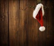 Weihnachts-Santa Claus Hat Hanging On Wood-Wand, Weihnachtskonzept stockfotos