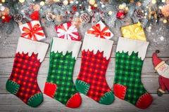 Weihnachts-Strumpf, der gegen hölzerne Wand mit Geschenkgeschenken und Weihnachten-decorstion hängt lizenzfreie stockfotografie