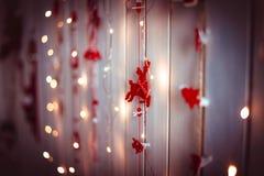 Weihnachts- und des neuen Jahresdekorationen mit roten Spielzeugrotwild und gelben den Lichtern, die an einer hölzernen Beschaffe Stockfoto