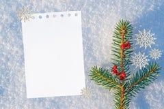 Weihnachts- und des neuen Jahreshintergrund leeres weißes Blatt Papier für Text, Grüße auf natürlichem Schnee mit einer blauen Tö Lizenzfreies Stockbild