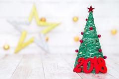 Weihnachts- und des neuen Jahreshintergrund mit roten hölzernen Tabellen 2018 nahe Weihnachtsbaum witn Licht und Stern auf dem Hi Lizenzfreies Stockfoto