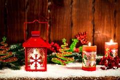 Weihnachts- und des neuen Jahreshintergrund mit Weihnachten leuchten Laterne und Weihnachtsbaumaste, Schnee und Dekorationen durc Stockbild