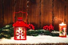 Weihnachts- und des neuen Jahreshintergrund mit Weihnachten leuchten Laterne und Weihnachtsbaumaste, Schnee und Dekorationen durc Stockfotos