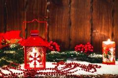 Weihnachts- und des neuen Jahreshintergrund mit Weihnachten leuchten Laterne und Weihnachtsbaumaste, Schnee und Dekorationen durc Stockbilder