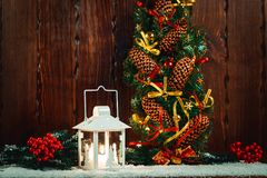 Weihnachts- und des neuen Jahreshintergrund mit Weihnachten leuchten Laterne und Weihnachtsbaumaste, Schnee und Dekorationen durc Lizenzfreie Stockfotografie