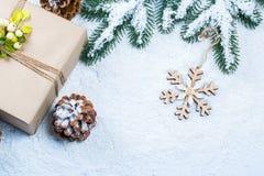 Weihnachts- und des neuen Jahreshintergrund mit Weihnachtsbaumasten auf Schnee und Dekorationen Freier Raum Stockfotografie