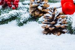 Weihnachts- und des neuen Jahreshintergrund mit Weihnachtsbaumasten auf Schnee und Dekorationen Freier Raum Lizenzfreie Stockfotos
