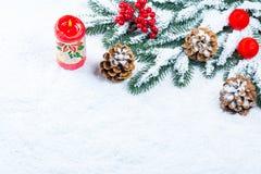 Weihnachts- und des neuen Jahreshintergrund mit Weihnachtskerze und Weihnachtsbaumasten Stockbild