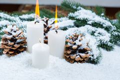 Weihnachts- und des neuen Jahreshintergrund mit Weihnachtskerze und Weihnachtsbaumasten auf Schnee Stockbilder