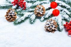 Weihnachts- und des neuen Jahreshintergrund mit Weihnachtskerze und Weihnachtsbaumasten auf Schnee und Dekorationen Stockbild