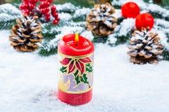 Weihnachts- und des neuen Jahreshintergrund mit Weihnachtskerze und Weihnachtsbaumasten auf Schnee und Dekorationen Stockfotografie