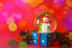 Weihnachts- und des neuen Jahreskarte mit Schneekugelschneemann nach innen Geschenkbox auf rotem bokeh Hintergrund Feiertags-, Wi stockfotografie