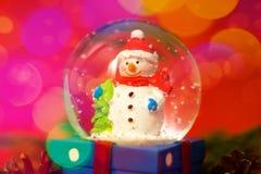 Weihnachts- und des neuen Jahreskarte mit Schneekugelschneemann nach innen Geschenkbox auf rotem bokeh Hintergrund Feiertags-, Wi lizenzfreie stockfotografie