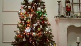Weihnachts- und des neuen Jahresspielwaren auf dem Weihnachtsbaum unter den funkelnden Lichtern stock video footage